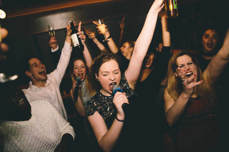 An image of a group of young people with drinks in their hands singing karaoke enthusiastically at Lucky Voice Islington