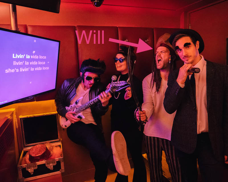 A group of three people in a karaoke booth singing along to La Vida Loca. One singer is dressed like Elvis, one is dressed like Audrey Hepburn, one is dressed like a pirate and the other is dressed like Charlie Chaplin. A pink arrow points at the singer dressed as a pirate identifying him as Will