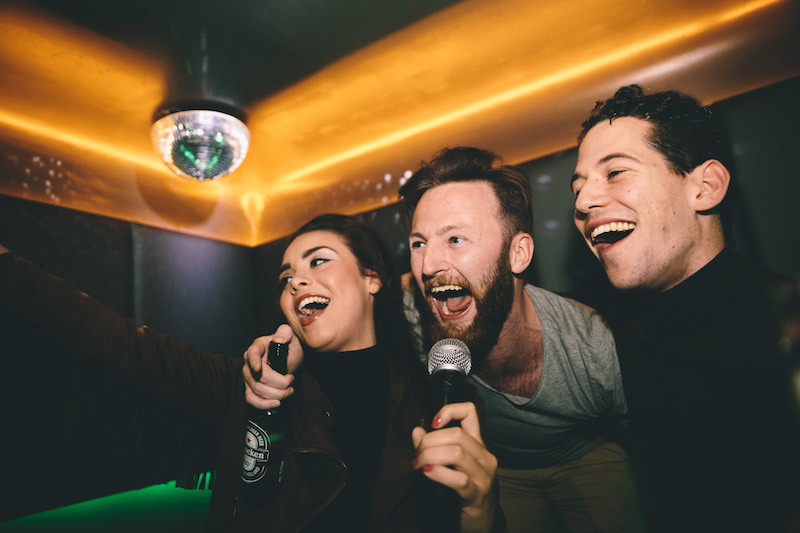 A photo of a man and two women singing karaoke together in a private room and having a great time