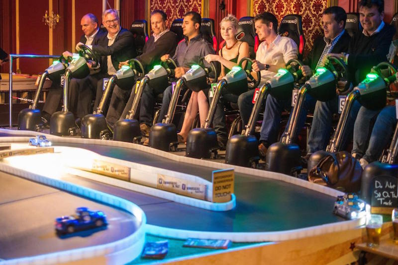 A group of people sat down at the Four Thieves pub playing on its giant scalextric track