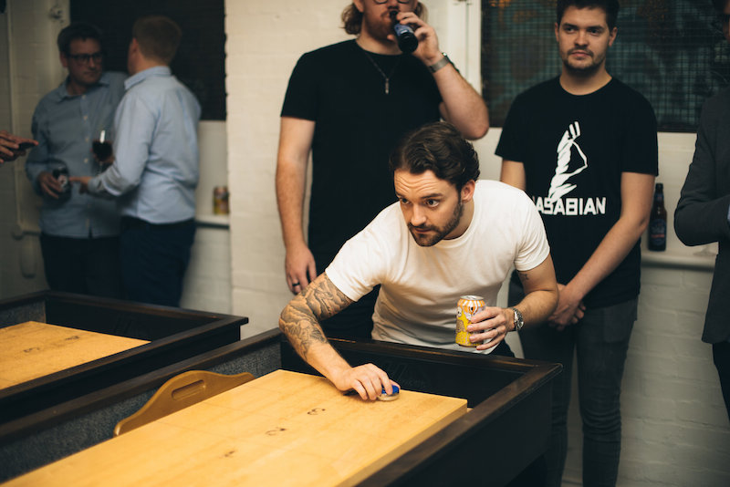 A man preparing to throw a counter in shuffleboard while holding a beer in his other hand