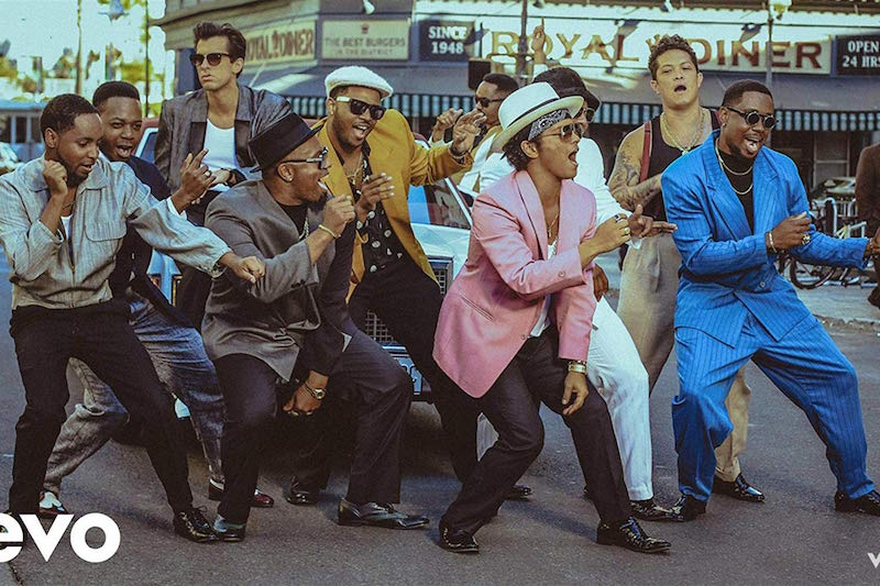 An image of Bruno Mars in the middle of singing Uptown Funk with his back up dancers. The image oozes confidence