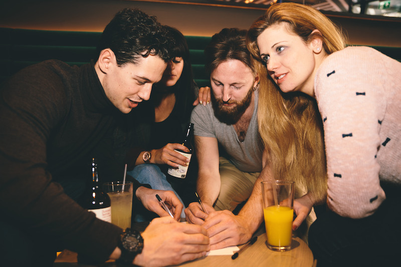 An image of a group of friends writing their answers down in the Lucky Voice Islington pub quiz