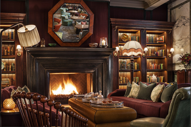 A photo of a roaring fire in the fireplace of Scarfes Bar in Holborn with leather chairs, an array of books and whisky on the table