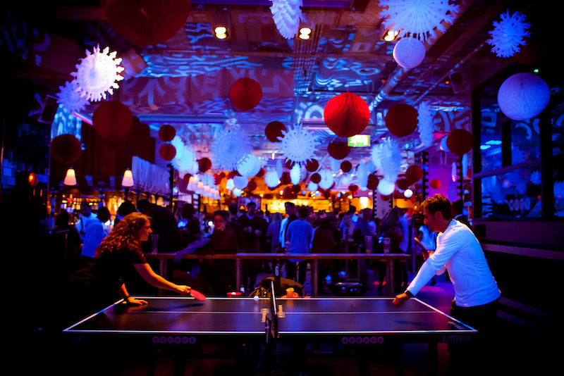 The interior of Bounce Farringdon at night with loads of UV ping pong tables and interesting lighting